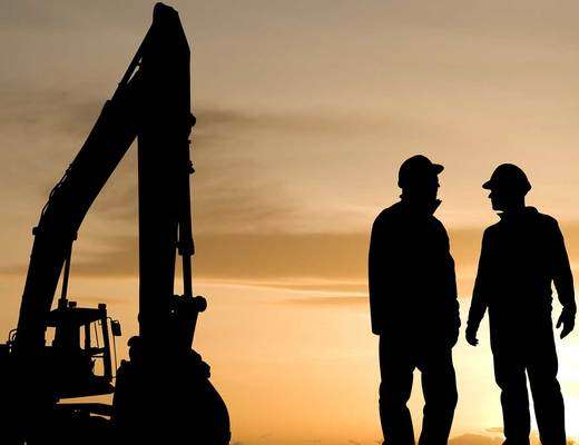 Construction workers standing next to an excavator at sunset