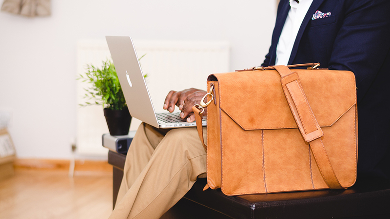 man typing on a laptop with a brown bag next to him