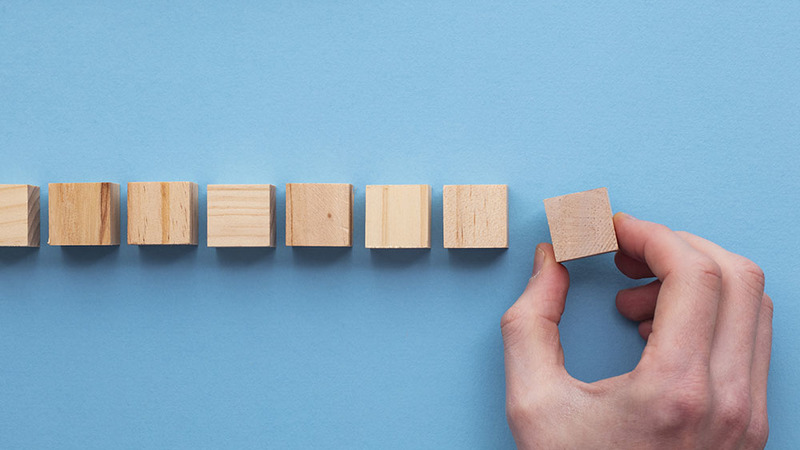 Hand placing a series of wooden blocks