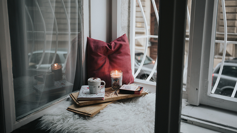 Candle and red pillow placed by a white window