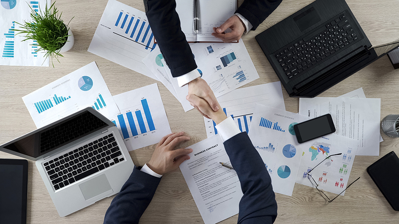 Men shaking hands across a desk with graphs and data