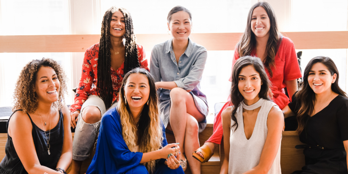 7 women in an office smiling together